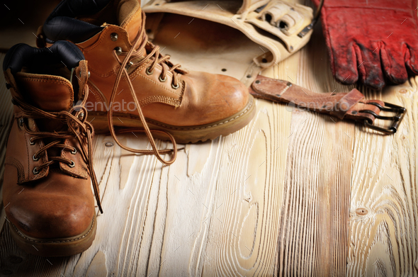 Yellow leather used work boots with tool belt and protective glo - Stock Photo - Images