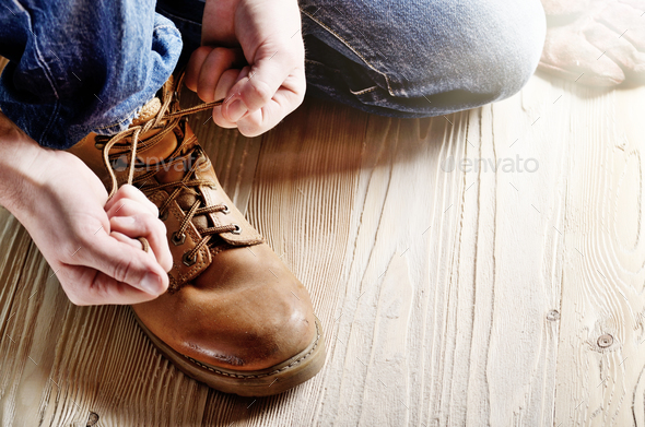 Carpenter in blue jeans tying shoelaces of yellow work boots on - Stock Photo - Images