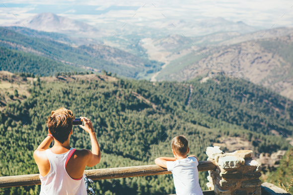 Young woman takes picture at the mountain - Stock Photo - Images