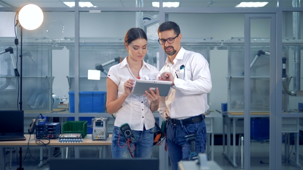Female and Male Engineers Are Discussing Something with a Tablet Computer