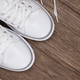 White sneakers on dark wooden surface - PhotoDune Item for Sale