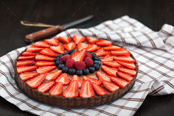Delicious chocolate tart decorated with fresh berries - Stock Photo - Images