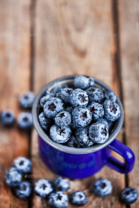 Fresh ripe blueberries and in blue enamel mug - Stock Photo - Images