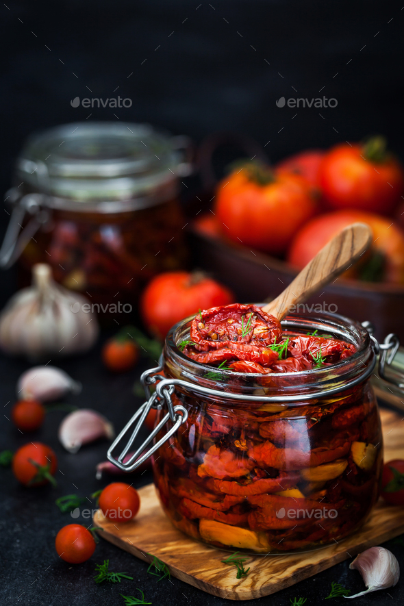 Sun dried tomatoes with garlic and olive oil in a jar - Stock Photo - Images