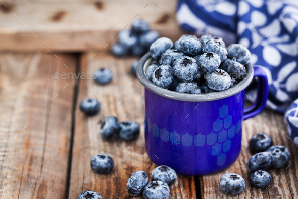 Fresh ripe blueberries and in blue enamel mug - Stock Photo - Images