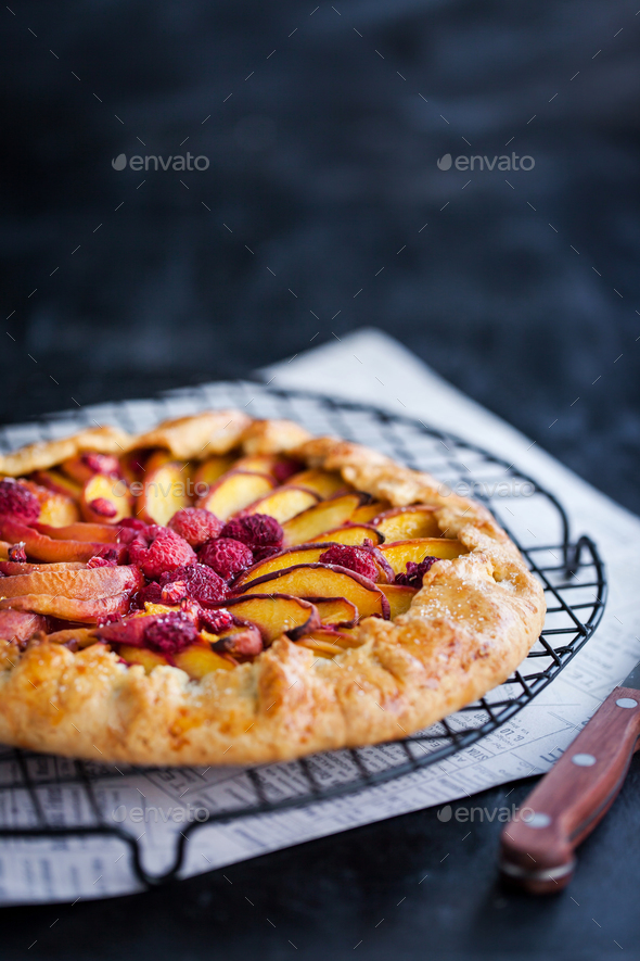 Galette with peach and raspberry on dark - Stock Photo - Images