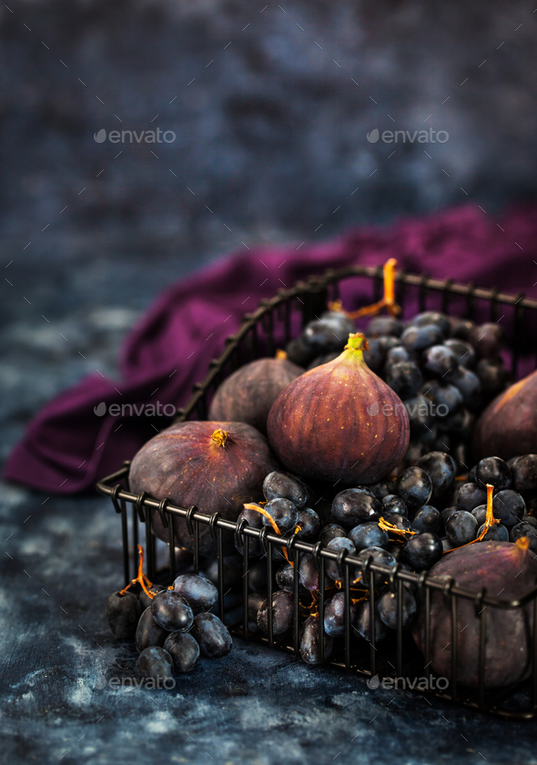 Fresh figs and purple grape in basket - Stock Photo - Images