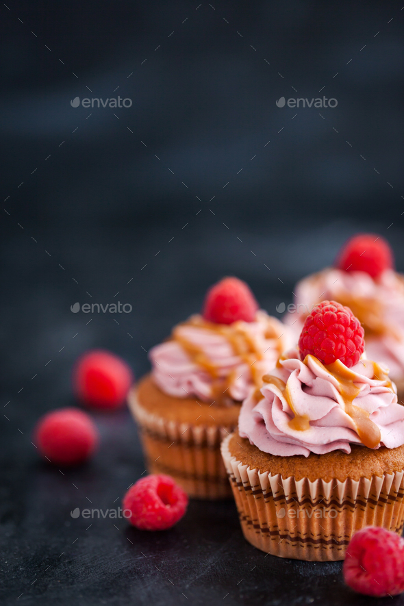 Raspberry and caramel cupcakes on dark background - Stock Photo - Images