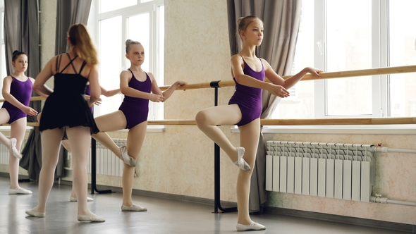 Serious Little Girls Learning Sequence Of Ballet Positions At Ballet