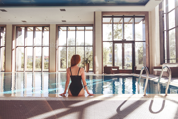 Enjoying vacation. Back view of slim young woman drinking cocktail in swimming pool. - Stock Photo - Images