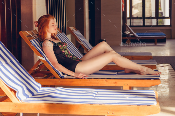 Portrait of pretty cheerful woman relaxing at the luxury poolside - Stock Photo - Images