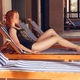 Portrait of pretty cheerful woman relaxing at the luxury poolside - PhotoDune Item for Sale
