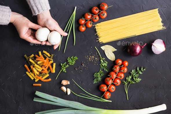 Close-up of women hands, choose foods vegetables, pasta, spices - Stock Photo - Images