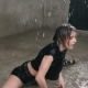 Wet Woman Dancer in Black Body Suit and Points Performs Modern Dance on the Floor in the Rain