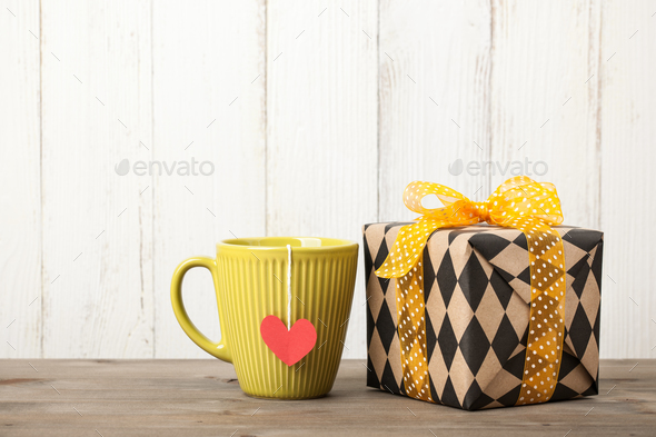 Wrapped gift box and cup on wooden table - Stock Photo - Images