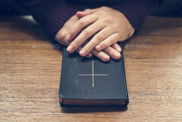 Hands over bible on wooden table - Stock Photo - Images