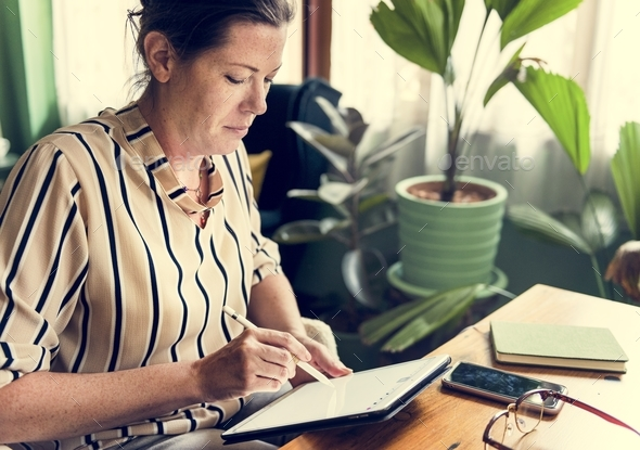 Caucasian woman writing to do list on tablet - Stock Photo - Images