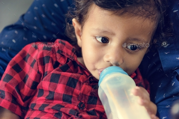 Young Indian boy drinking milk from bottle - Stock Photo - Images