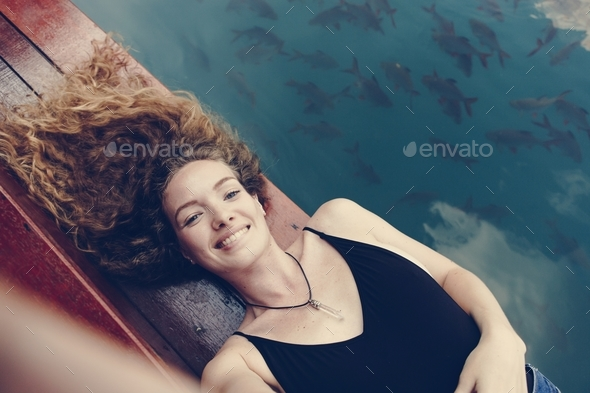 Woman relaxing on a wooden jetty - Stock Photo - Images