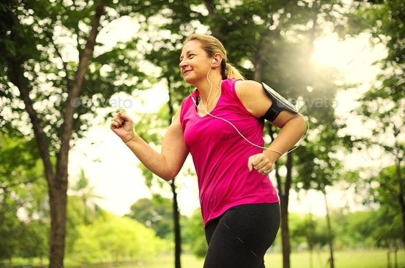 Mature woman jogging in the park - Stock Photo - Images