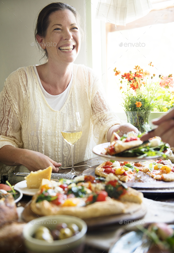 Woman enjoying a pizza dinner - Stock Photo - Images