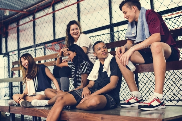 Group of young teenager friends sitting on a bench relaxing - Stock Photo - Images
