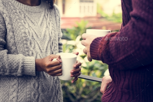 Young couple sipping hot drink together - Stock Photo - Images