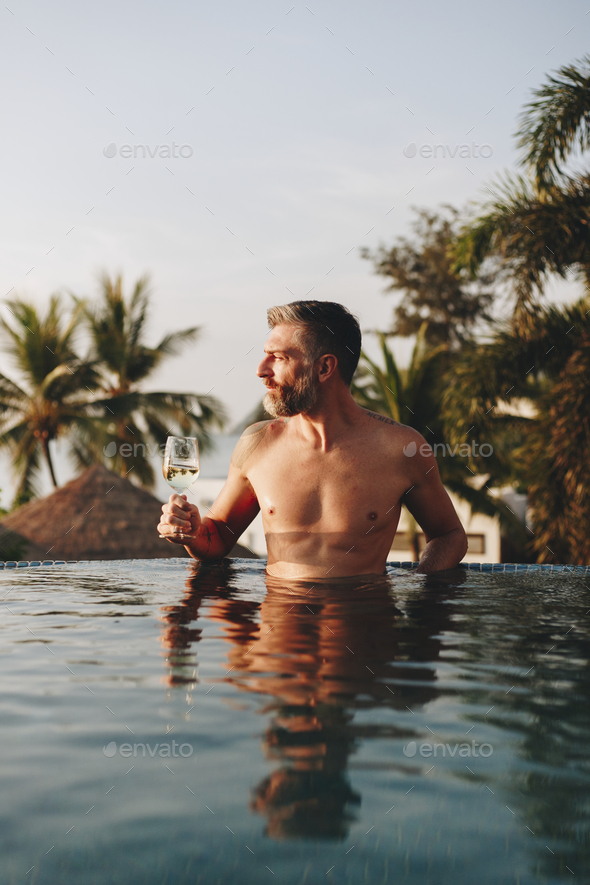 Man drinking wine in a swimming pool - Stock Photo - Images