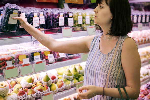 Woman selecting some grapes at the supermarket - Stock Photo - Images