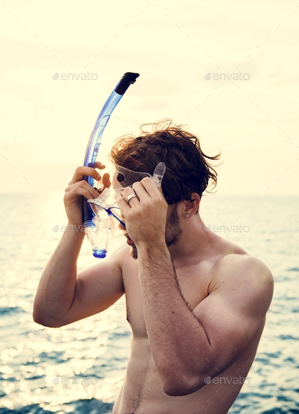 Caucasian guy preparing for snorkeling - Stock Photo - Images