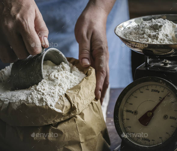 Baker weighing flour on a scale - Stock Photo - Images