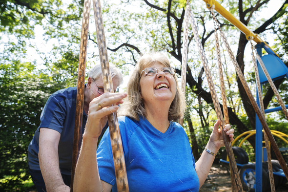 Senior couple playing at a playground - Stock Photo - Images