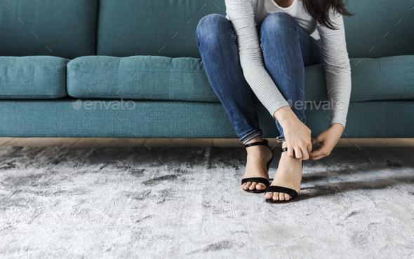 Woman sitting on sofa to wearing high heels - Stock Photo - Images