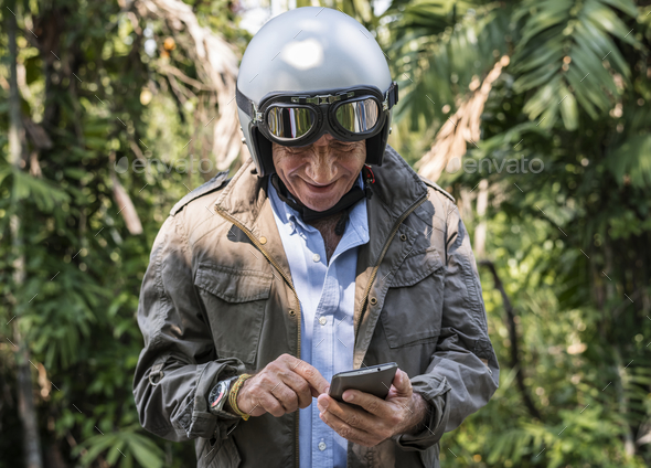 Mature biker checking his phone - Stock Photo - Images