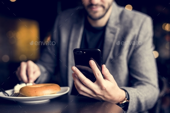 Man reading messages on his phone - Stock Photo - Images