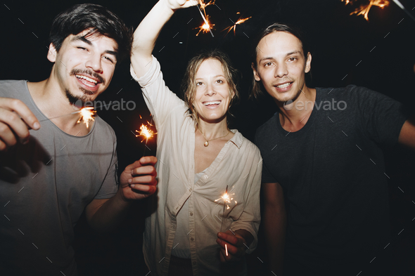 Two Caucasian men and a woman playing with sparklers celebration and festive party concept - Stock Photo - Images