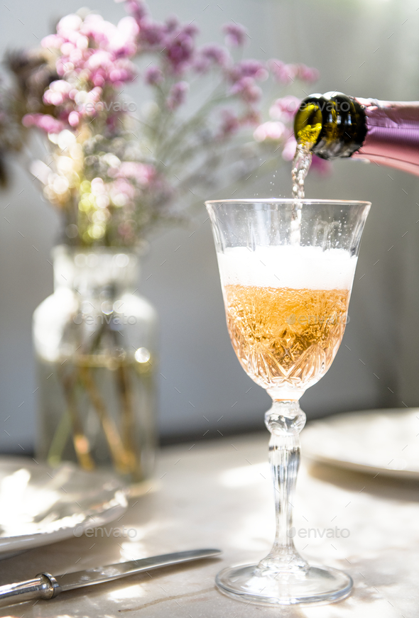 Pouring champagne into a glass - Stock Photo - Images