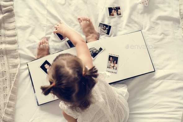 Little girl playing with a photo album - Stock Photo - Images