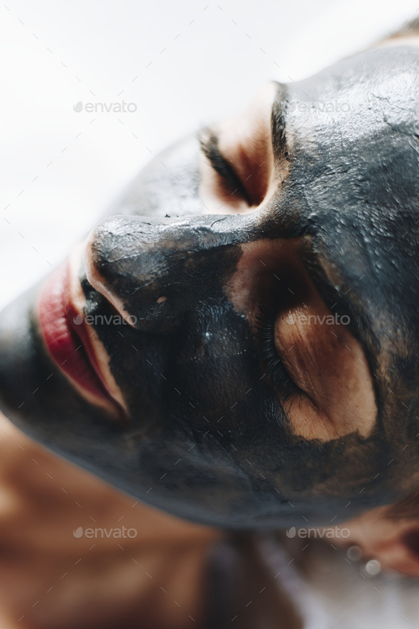 Woman relaxing with a charcoal facial mask - Stock Photo - Images