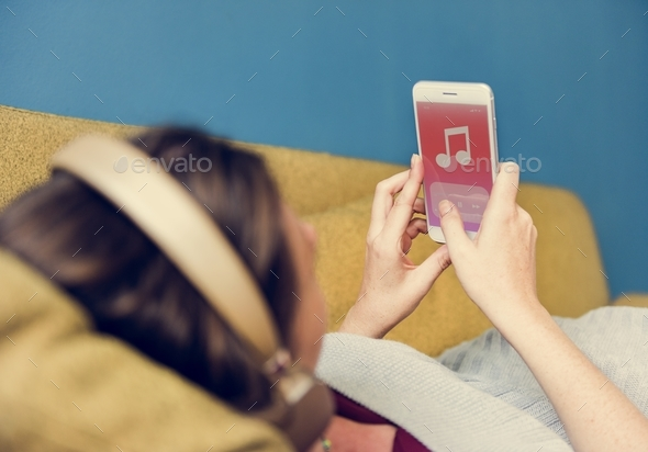 Woman listening to music on the sofa - Stock Photo - Images