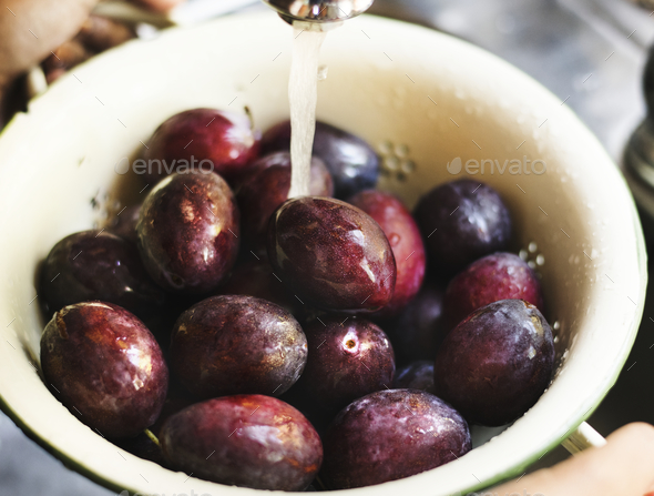 Organic plums being washed under running water food photography recipe idea - Stock Photo - Images