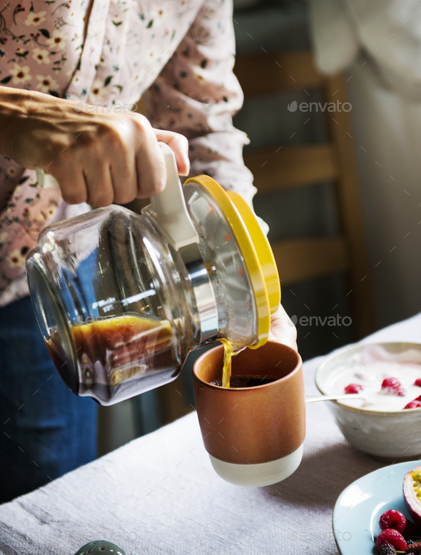 Woman serving hot coffee for breakfast - Stock Photo - Images