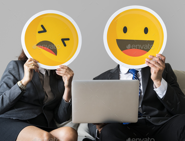 Cheerful people holding emoticon icon - Stock Photo - Images