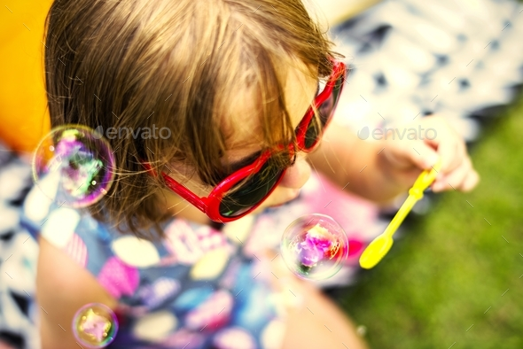 Young girl enjoying blowing soap bubbles - Stock Photo - Images