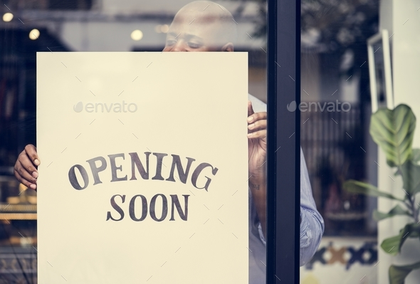 Man putting on store opening soon sign - Stock Photo - Images