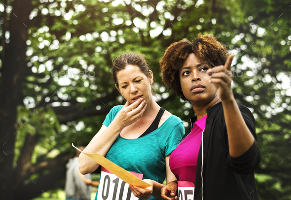 Women looking at the map for orienteering box location - Stock Photo - Images
