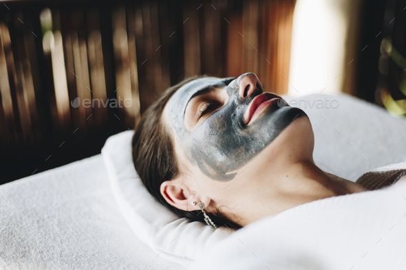 Woman relaxing with a facial mask at the spa - Stock Photo - Images