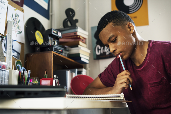 Teenage boy in a bedroom doing work thinking - Stock Photo - Images
