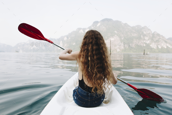 Woman paddling a canoe through a national park - Stock Photo - Images