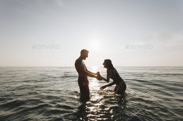 Couple playing in the water - Stock Photo - Images